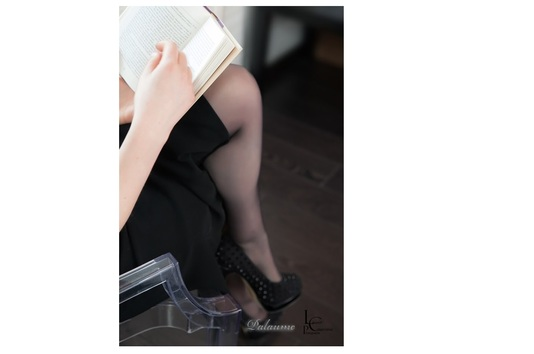 Palaume est en pleine lecture de son roman. Femme sexy avec jambes croisés