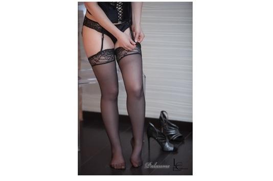 Jeune femme séduisante en train de mettre ses bas avec son porte jarretelles