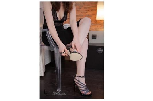 Femme en robe noire sexy et chaussures strass à talon
