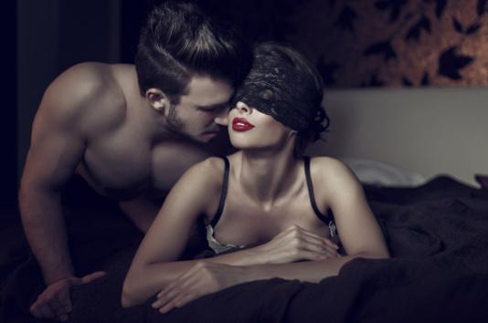 Une couple dans un lit - femme avec les yeux bandés