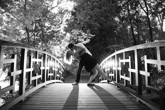 couple romantique en train de s'embrasser sous un pont